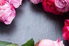 Marco rojo y rosado de las rosas en la tabla Imagen de archivo