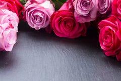 Marco rojo y rosado de las rosas en la tabla Foto de archivo libre de regalías