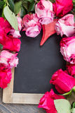 Marco rojo y rosado de las rosas en la tabla Imágenes de archivo libres de regalías
