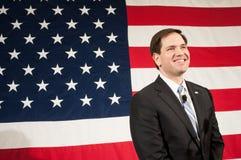 Marco Rubio sonríe antes de una bandera americana Imagen de archivo