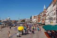 意大利,威尼斯- 2012年7月:有旅游近的圣Marco广场人群的威尼斯江边2012年7月16日的在威尼斯。St Marco Squar 库存照片