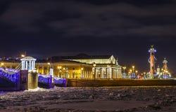 Marco turístico em St Petersburg, Rússia: o cuspe da ilha de Vasilievsky iluminado na noite do inverno com o histórico imagens de stock