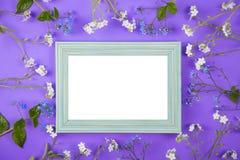 Marco vacío de la foto rodeado con las pequeñas flores azules y blancas en el fondo violeta Foto de archivo