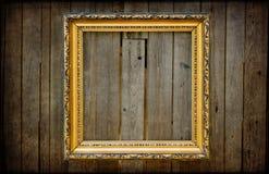 Marco vacío de oro en una pared rústica de madera Imagenes de archivo