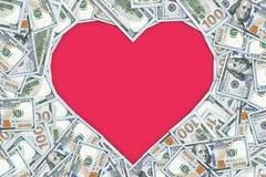 Marco vacío en forma de corazón hecho con muchos billetes de banco de 100 dólares Foto de archivo