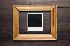 Marco vacío y foto vieja en fondo de madera imagen de archivo