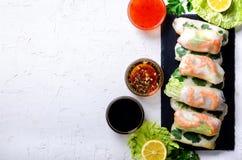 Marco vietnamita, asiático, chino fresco de la comida en el fondo concreto blanco Papel de arroz de los rollos de primavera, lech imagenes de archivo