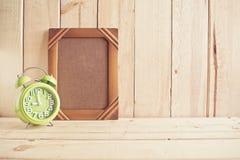 Marco y reloj viejos de la foto en la tabla de madera sobre el fondo de madera Fotos de archivo