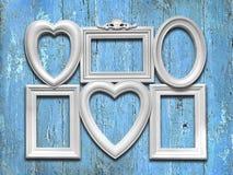 Marcos blancos decorativos de la foto en un fondo de madera azul Foto de archivo