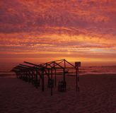 Marcos de la choza de la playa silueteados contra el cielo rojo vivo de la puesta del sol fotografía de archivo