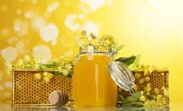 Marcos de madera con los panales y el tarro de miel en fondo amarillo Fotos de archivo