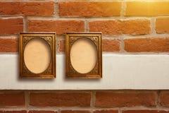 Marcos de madera dorados para las imágenes en la pared de ladrillo vieja Foto de archivo libre de regalías