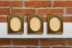 Marcos de madera dorados para las imágenes en la pared de ladrillo vieja Fotos de archivo