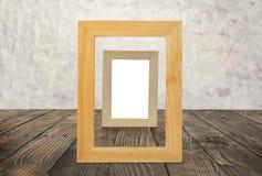 Marcos de madera en blanco en el piso de madera marrón Imagen de archivo libre de regalías
