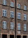 Marcos de ventana blancos en las paredes de ladrillo de Brown Foto de archivo