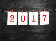 Marcos del papel o de la foto con 2017 figuras que cuelgan en la cuerda rayada roja Diseño del Año Nuevo En fondo de madera Foto de archivo