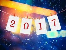 Marcos del papel o de la foto con 2017 figuras que cuelgan en la cuerda rayada roja Fondo de las nevadas, diseño del Año Nuevo Imagenes de archivo