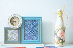 Marcos en blanco de la foto con los relojes viejos y la botella decorativa Imagen de archivo libre de regalías
