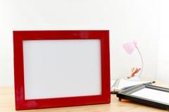 Marcos en blanco de la foto en la tabla de madera y el fondo blanco Imagen de archivo