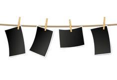 Marcos en blanco de la foto en una cuerda para tender la ropa Imagen de archivo libre de regalías