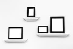Marcos en blanco múltiples en las repisas en una pared Imágenes de archivo libres de regalías