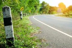 Marcos miliários preto e branco com a borda da estrada da grama verde, estrada das árvores foto de stock