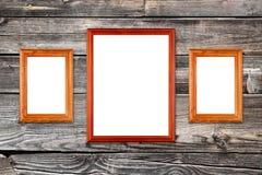Marcos vacíos de la foto en la pared de madera Fotos de archivo libres de regalías