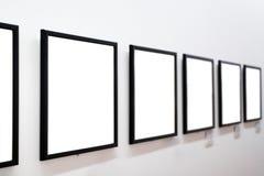 Marcos vacíos en la pared blanca Imagenes de archivo