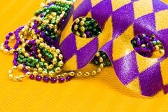 Mardi Gras. Beads and mask on yellow backgound Stock Image