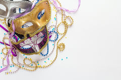 Mardi Gras background with masks, beads and copy space. Carnivale mask on a white background