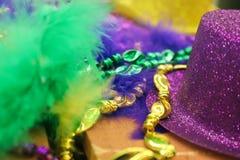 Mardi Gras bakgrund i gräsplan och skuggor av lilor och guld med fjädrar och sparkly hatt och pärlor - selektiv fokus arkivbilder