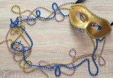 Mardi Gras bakgrund med den guld- maskeringen, pärlor och kopieringsutrymme royaltyfri foto