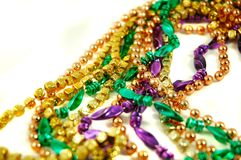 Mardi Gras Beads. Strands of Mardi Gras beads isolated on a white background