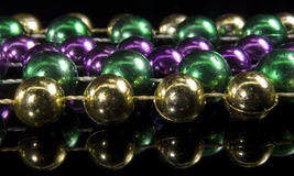 Mardi Gras beads. Reflection of mardi gras beads on black surface Stock Image