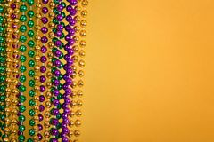 Mardi Gras beads against golden yellow background Stock Photography