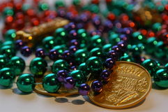 Mardi gras beads and coins. Shiny green, red, and purple Mardi Gras beads and fake gold coins Royalty Free Stock Images