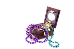 Mardi Gras Beads in Jewelry Box. Three strands of Mardi Gras beads in a small wooden jewelry box, isolated against white background royalty free stock images