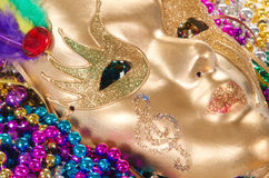 Mardi Gras beads and mask. Colorful Mardi Gras beads and a golden mask