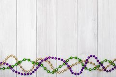 Mardi Gras beads on white wooden backgound.  royalty free stock images
