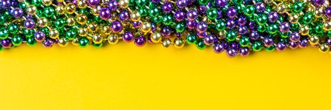 Mardi gras carnival background - beads and mask. On yellow background