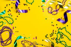 Mardi gras carnival concept - beads on yellow background. Top view royalty free stock photography
