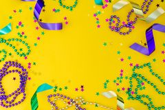 Mardi gras carnival concept - beads on yellow background royalty free stock photos