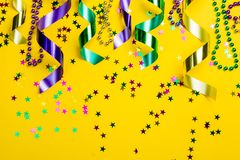 Mardi gras carnival concept - beads on yellow background stock photography