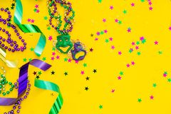 Mardi gras carnival concept - beads on yellow background royalty free stock photo