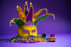 Mardi Gras or Carnivale mask on purple. Festive mardi gras, venetian or carnivale mask on a purple background stock images