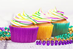 Mardi Gras cupcakes and beads Royalty Free Stock Images