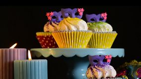 Mardi Gras Cupcakes. With purple mask toppers with burning candles, slow zoom in and out stock footage
