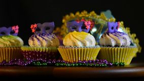 Mardi Gras Cupcakes. With purple mask toppers on revolving table stock video footage