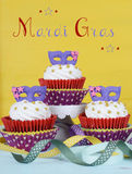 Mardi Gras cupcakes. With purple mask toppers on rustic style vintage yellow and aqua blue wood background with text