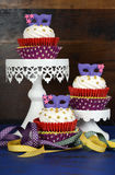Mardi Gras cupcakes with purple mask toppers on rustic style wood background. Royalty Free Stock Images